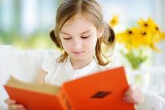 读一本书的可爱的小女孩在白色客厅在夏日 免版税库存图片