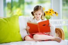 读一本书的可爱的小女孩在白色客厅在夏日 库存照片