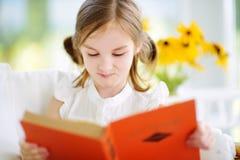 读一本书的可爱的小女孩在白色客厅在夏日 免版税库存照片