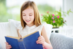 读一本书的可爱的小女孩在白色客厅 免版税库存照片