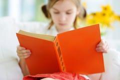 读一本书的可爱的小女孩在白色客厅 免版税图库摄影