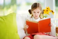 读一本书的可爱的小女孩在白色客厅 免版税库存图片