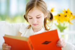 读一本书的可爱的小女孩在白色客厅 图库摄影
