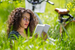 读一本书的可爱的年轻深色的妇女在公园 免版税库存照片