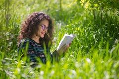 读一本书的可爱的年轻深色的妇女在公园 库存图片