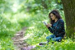 读一本书的可爱的年轻深色的妇女在公园 图库摄影