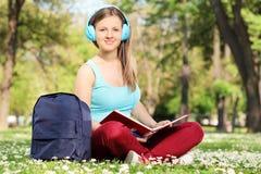 读一本书的女学生在公园 免版税库存图片