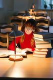 读一本书的女孩在图书馆里在灯下 免版税库存照片