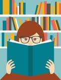 读一本书的女孩在图书馆里 免版税库存图片