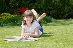 读一本书的女孩在庭院里 库存图片