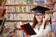 读一本书的女性学校学生在图书馆里 免版税图库摄影