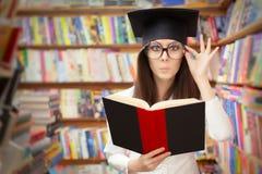 读一本书的好奇学校学生在图书馆里 免版税库存照片