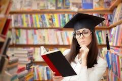 读一本书的好奇学校学生在图书馆里 库存图片