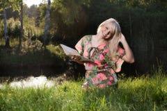 读一本书的妇女在公园 免版税图库摄影