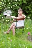 读一本书的妇女在庭院里 库存照片