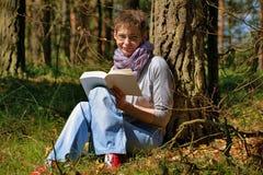 读一本书的妇女在森林里 免版税库存照片