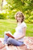 读一本书的孕妇在公园 免版税图库摄影