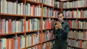 读一本书的学生在图书馆里在电话 股票视频