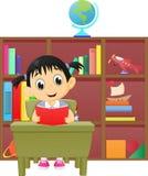 读一本书的小女孩在图书馆里 免版税库存照片