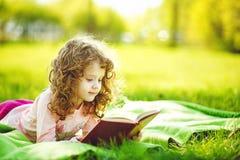 读一本书的小女孩在春天公园 免版税库存照片
