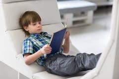 读一本书的小男孩孩子在图书馆里 免版税图库摄影