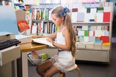 读一本书的小聪明的女孩在学校图书馆里 免版税库存图片