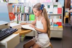 读一本书的小聪明的女孩在学校图书馆里 免版税库存照片
