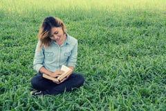 读一本书的少妇在公园在草 库存图片