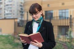 读一本书的少妇在城市 免版税库存图片