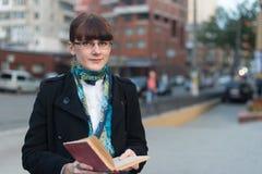 读一本书的少妇在城市 库存图片