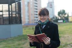 读一本书的少妇在城市 免版税库存照片