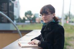 读一本书的少妇在城市 库存照片