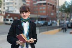 读一本书的少妇在城市 免版税图库摄影