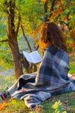 读一本书的少妇在秋天公园 库存图片