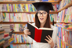 读一本书的惊奇的学校学生在图书馆里 库存照片