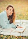 读一本书的逗人喜爱的女孩在公园 库存图片