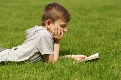 读一本书的逗人喜爱的白肤金发的男孩在公园 免版税图库摄影