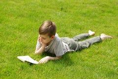 读一本书的逗人喜爱的白肤金发的男孩在公园 免版税库存照片