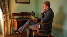 读一本书的年轻商人在一间老fahioned装饰的屋子 股票视频