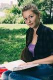 读一本书的年轻学生女孩在公园 库存照片