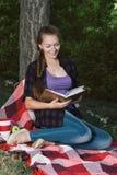 读一本书的年轻学生女孩在公园 库存图片