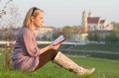 读一本书的年轻性感的妇女在维尔纽斯,立陶宛 库存图片