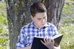 读一本书的年轻男孩在有浅景深的森林 免版税库存图片