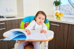 读一本书的滑稽的小孩女孩在厨房里 免版税库存照片