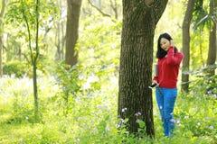一本亚洲中国自由妇女阅读书和听的画象到音乐在春天秋天公园在森林里 库存照片