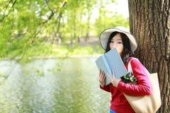 一本亚洲中国自由妇女阅读书的画象坐树由一条河在春天秋天公园 免版税库存图片