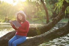 一本亚洲中国自由妇女阅读书的画象坐树由一条河在春天秋天公园 免版税库存照片