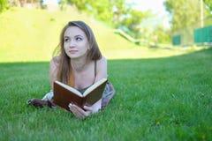 一本华美的年轻深色的户外学生阅读书的画象 免版税库存照片