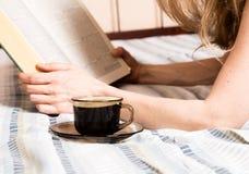 读一本厚实的书的美丽的妇女说谎在床,特写镜头咖啡杯 免版税库存照片