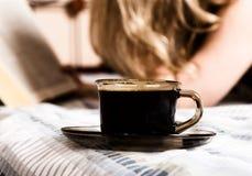 读一本厚实的书的美丽的妇女说谎在床,特写镜头咖啡杯 库存照片